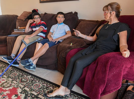 Visiting again from Uzbekistan (from left) Abdul Saidov, 15, and his friend Doni Musaev, 14, sit wearing their prosthetic legs while with Abdul's cousin Julie Scott at Scott's home on Monday, March 25, 2019, in Indian River County. The boys, who are best friends, were hit by a speeding car while in Uzbekistan in February, 2017, resulting in Abdul losing both legs, and Doni, losing his right leg below the knee, and have been returning to the United States to receive treatment for their injuries at the Shriners Hospital for Children in Tampa.