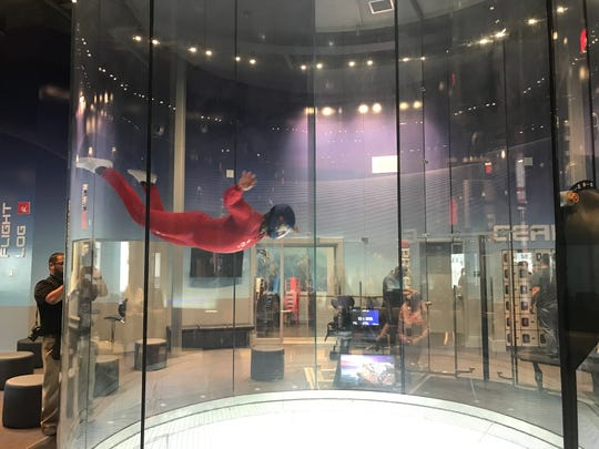 Flight instructors give demonstrations of indoor skydiving at the iFly business.