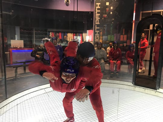 A flight instructor helps first-time flyer Karen Cowell hold steady inside the wind tunnel at iFly Indoor Skydiving.