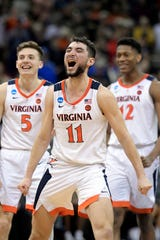 Virginia's Ty Jerome (11) celebrates with teammates Kyle Guy (5) and De'Andre Hunter (12) during overtime of the men's NCAA Tournament college basketball South Regional final game against Purdue, Saturday, March 30, 2019, in Louisville, Ky. Virginia won 80-75.