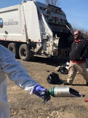 Sanitation Supervisor Jason Leary looks at a damaged oxygen cylinder recovered from the City sanitation vehicle that was collecting trash on Vandever Avenue this morning when two employees were injured.