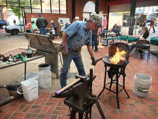 Blacksmith Larry Roderick pumps up the heat on his metal forge as he prepares to demonstrate metalworking in the Farmers Market at the After Hours Artwalk. Artists of all types display and sell their work at the monthly event.