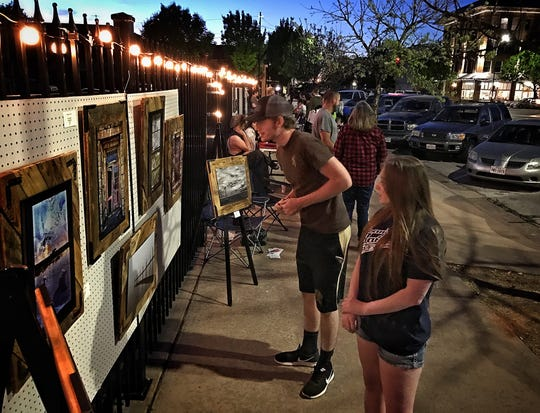 After Hours Artwalk attendees check out artwork along a fence line near The Holt in this 2017 file photo.