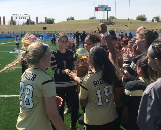 The Rider girls soccer team celebrates its 2-1 victory over El Paso High Friday at Grande Communications Stadium in Midland.
