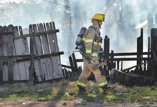 In this file photo, firefighter walks by a fence at the sight of a fire in the 2200 block of Holliday Road. The city is considering a bid for turnout gear extractor washer systems that will be installed at seven of the city's eight fire stations.