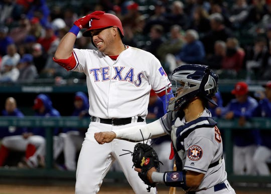 Texas Rangers' Asdrubal Cabrera holds his helmet after a strike call in the eighth inning of a baseball game as Houston Astros catcher Robinson Chirinos returns to the ball to relief pitcher Ryan Pressly, not pictured, in Arlington, Texas, Monday, April 1, 2019. (AP Photo/Tony Gutierrez)