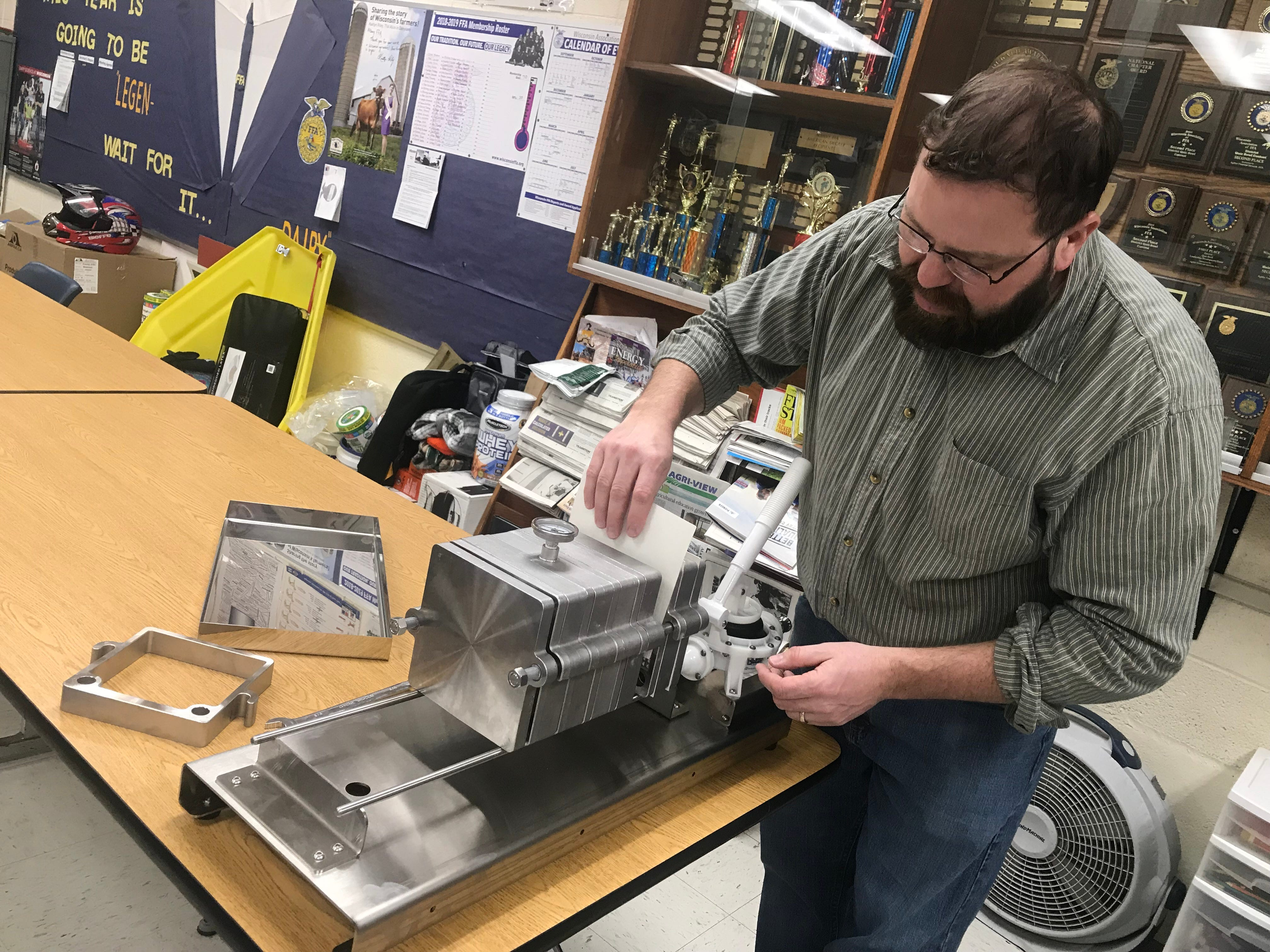 Agriculture Educator Jamie Rupp demonstrates a filter press for students in Albany.