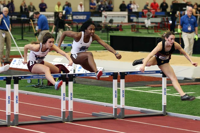 Zanesville grad Tiara Wiggins, middle, clears a hurdle during a race for Grand Valley State during her senior season. Wiggins finished as a two-time All-American and hopes to be veterinarian.
