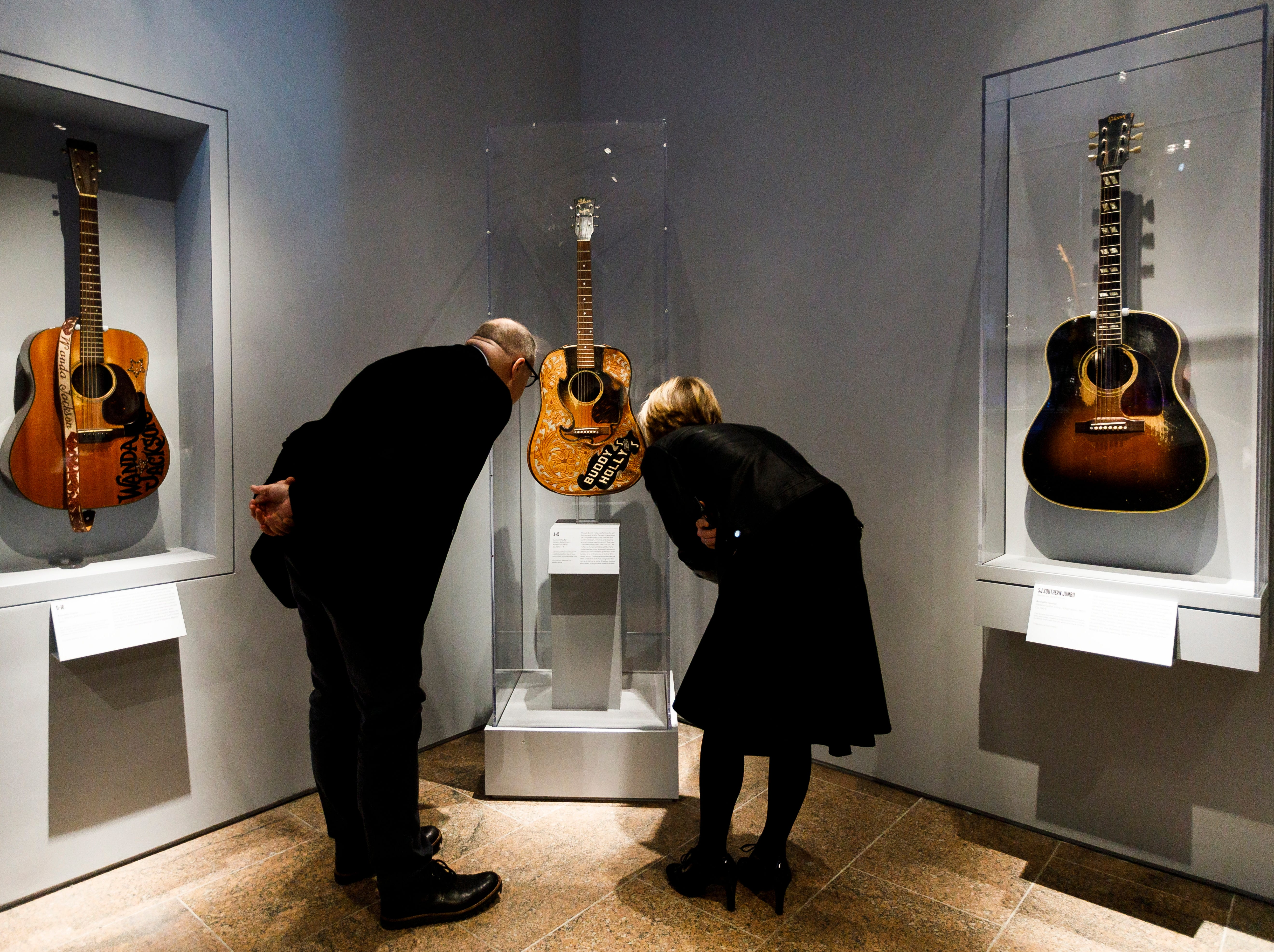 """Two people look at guitars owned by Buddy Holly, center, with guitars owned by Wanda Jackson, left, and Don Everly during a preview of the new exhibit """"Play It Loud: Instruments of Rock & Roll"""" at the Metropolitan Museum of Art in New York, New York on April 1, 2019. The exhibit features over 130 musical instruments, including many electric guitars, from iconic rock and roll musicians dating from 1939 to 2017 including The Beatles, Chuck Berry, Jimmy Page, Elvis Presley, and Jimi Hendrix. It runs from April 8 until October 1, 2019."""