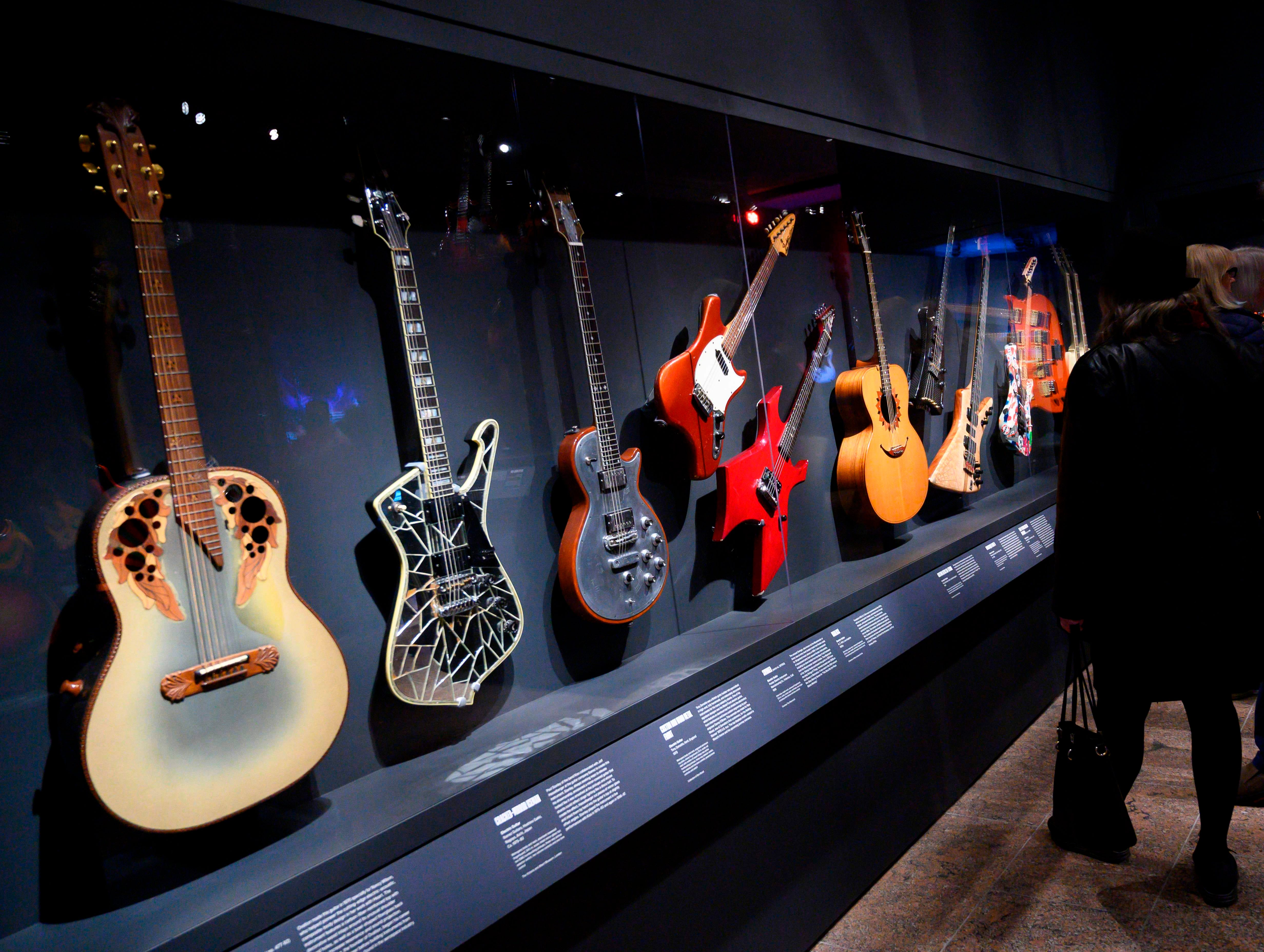 """Members of the media get a look at a group of guitars during a media preview for an exhibit called """"Play It Loud: Instruments of Rock and Roll"""" at the Metropolitan Museum of Art in New York on April 1, 2019."""