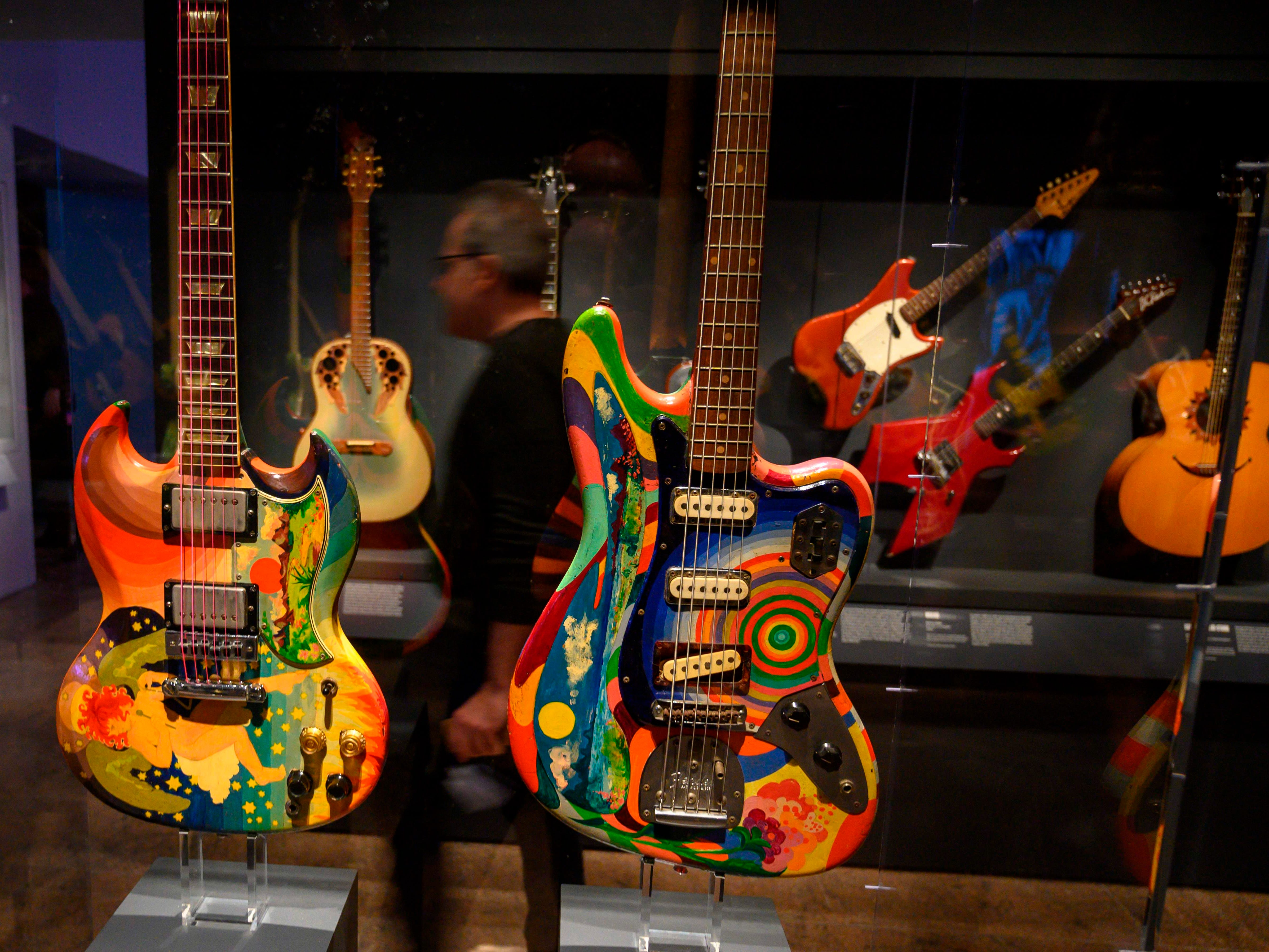 A reporter makes his way through a group of electric guitars.