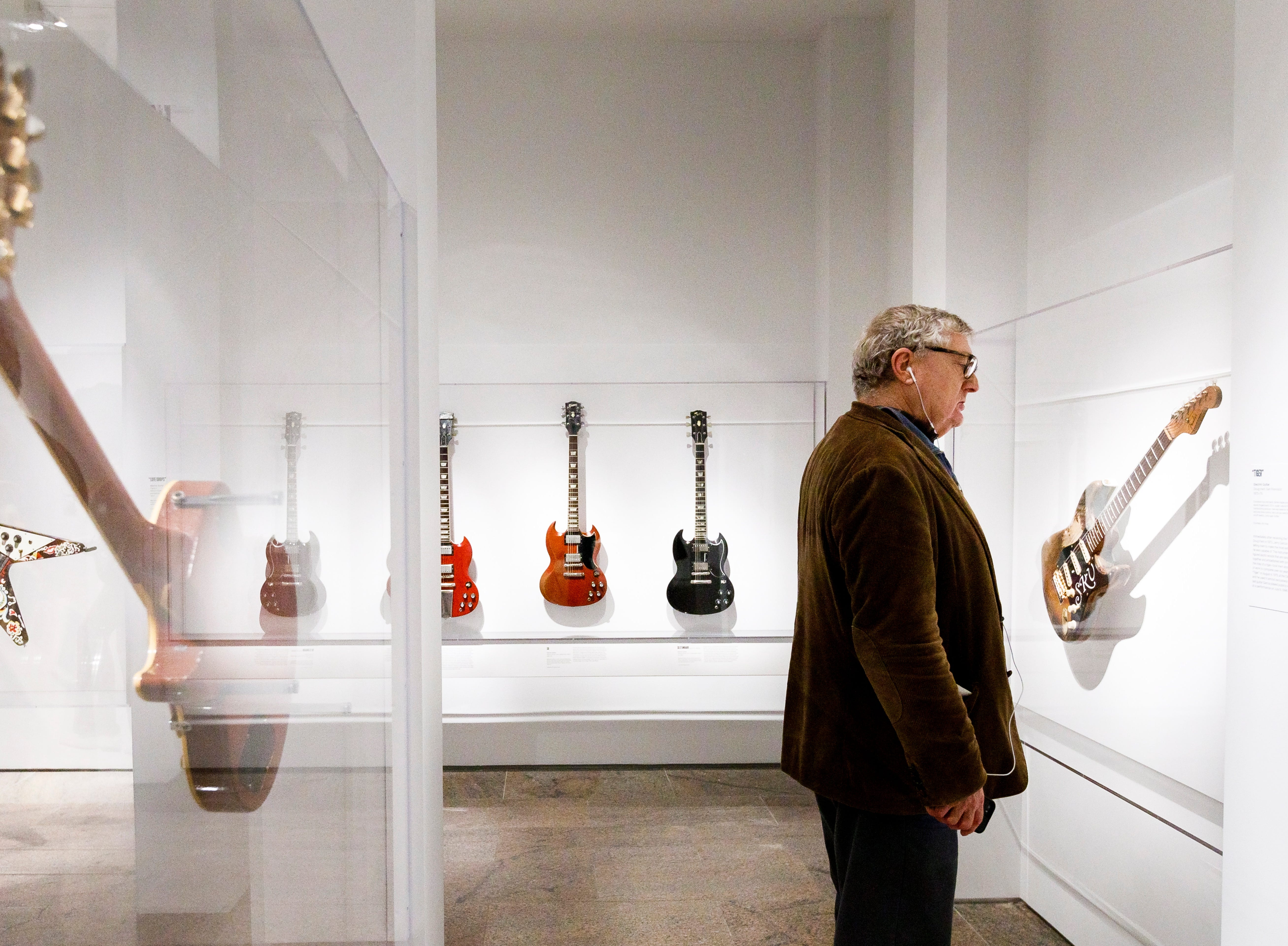 """A man looks at a guitar played by Stevie Ray Vaughn during a preview of the new exhibit """"Play It Loud: Instruments of Rock & Roll""""."""
