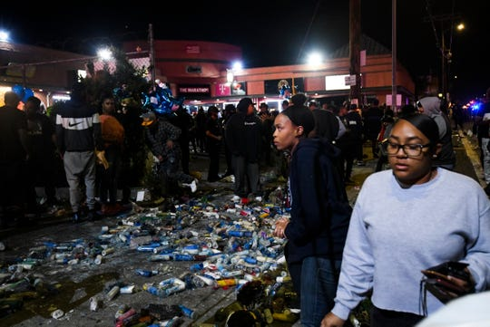 People walk past a pile of broken candles that were stepped on at the corner of Slauson and Crenshaw after multiple people were stabbed during a vigil for Nipsey Hussle on April 1, 2019 in Los Angeles.