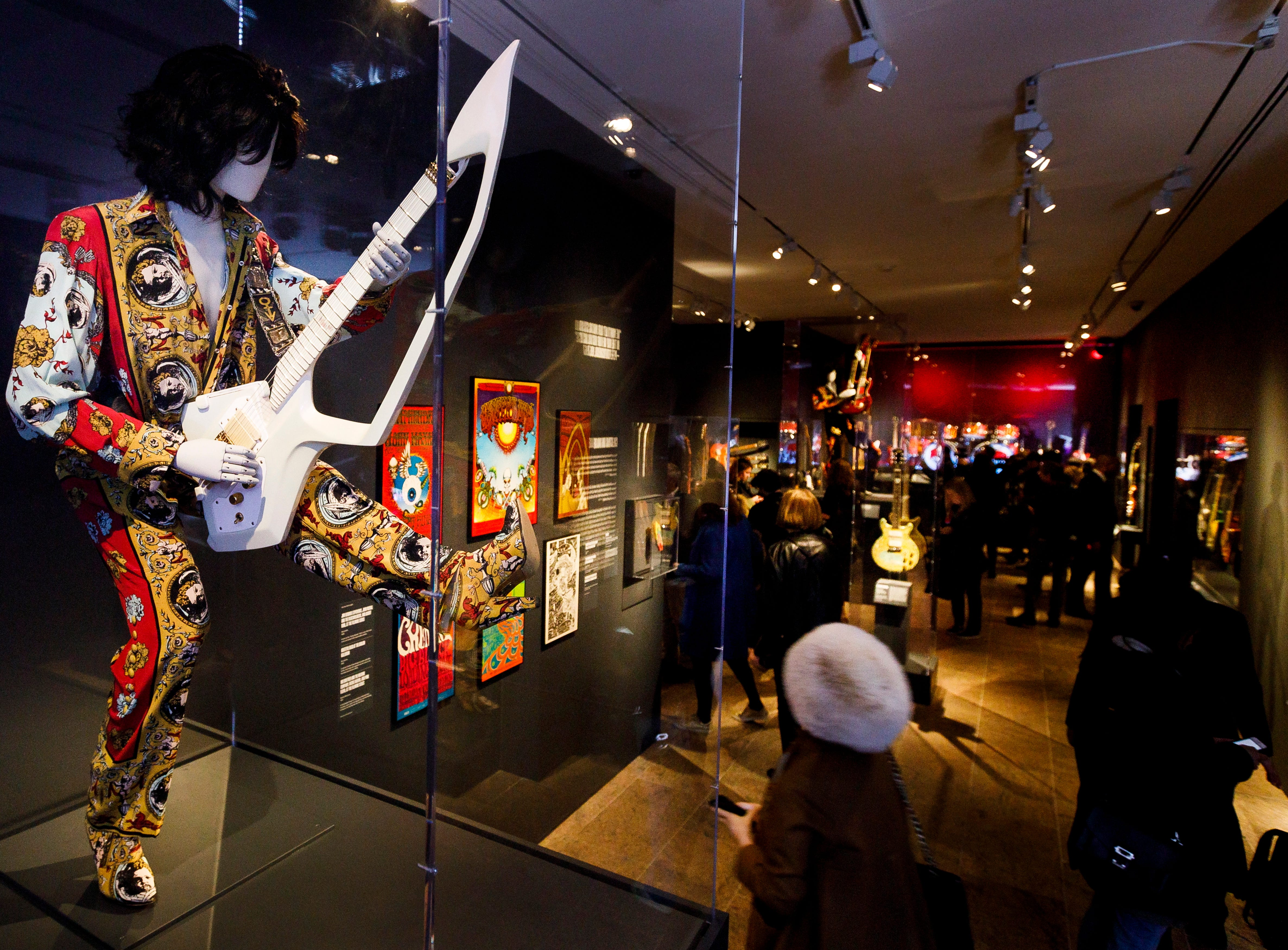 """A guitar and outfit owned by Prince is seen during a preview of the new exhibit """"Play It Loud: Instruments of Rock & Roll"""". The exhibit features over 130 musical instruments, including many electric guitars, from iconic rock and roll musicians dating from 1939 to 2017 including The Beatles, Chuck Berry, Jimmy Page, Elvis Presley, and Jimi Hendrix."""