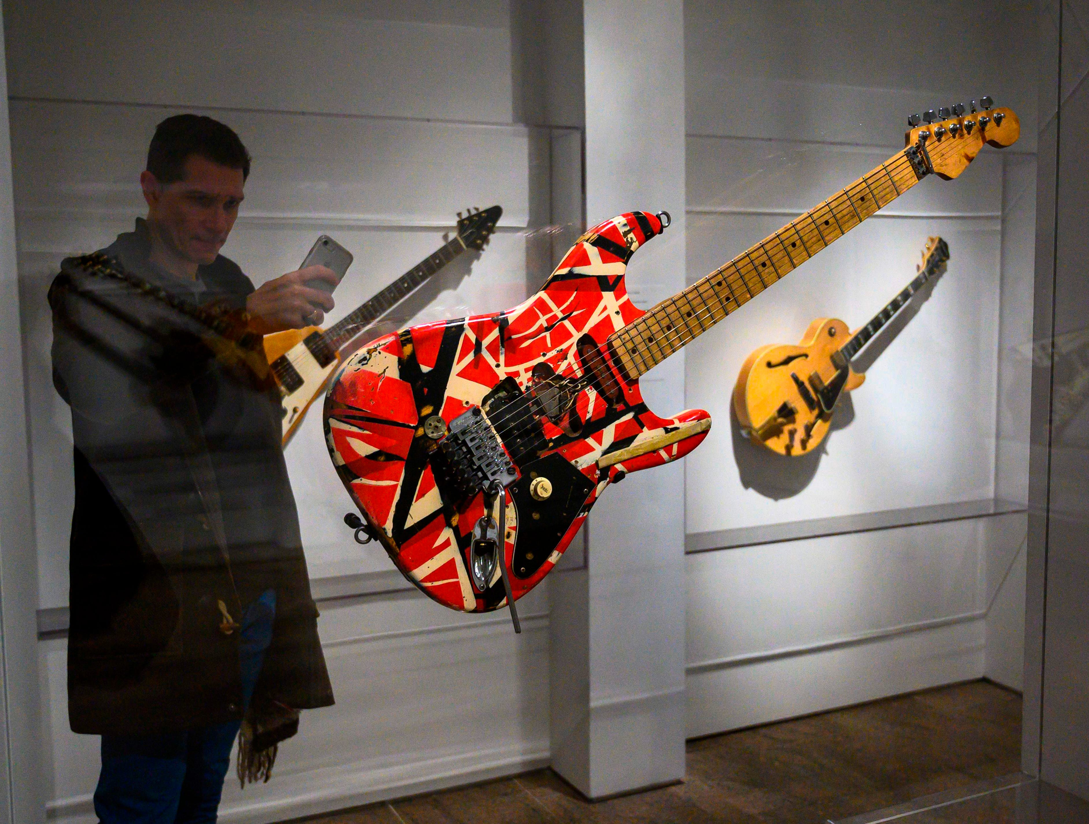 """A reporter takes a photo of """"Frankenstein"""", a guitar used by Eddie Van Halen, during a media preview for an exhibit called """"Play It Loud: Instruments of Rock and Roll"""" at the Metropolitan Museum of Art in New York on April 1, 2019."""