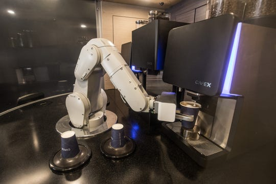 "A robot makes coffee drinks at Cafe X in downtown San Francisco. The company has three locations in the Bay Area, and soon will open up at the local airport. Founder Henry Hu says offloading the task of ""pushing coffee machine buttons"" to robots frees up humans to consult with customers on their order."