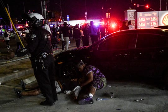 An injured man is tended to after being stabbed on April 1, 2019 in Los Angeles outside of Nipsey Hussle's clothing store.