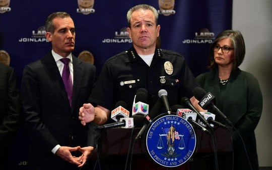 Los Angeles Mayor Eric Garcetti, left, listens as LAPD Chief Michael Moore addresses the media Tuesday about the investigation into the shooting death of rapper Nipsey Hussle and its plan to stem the recent tide of gang violence.