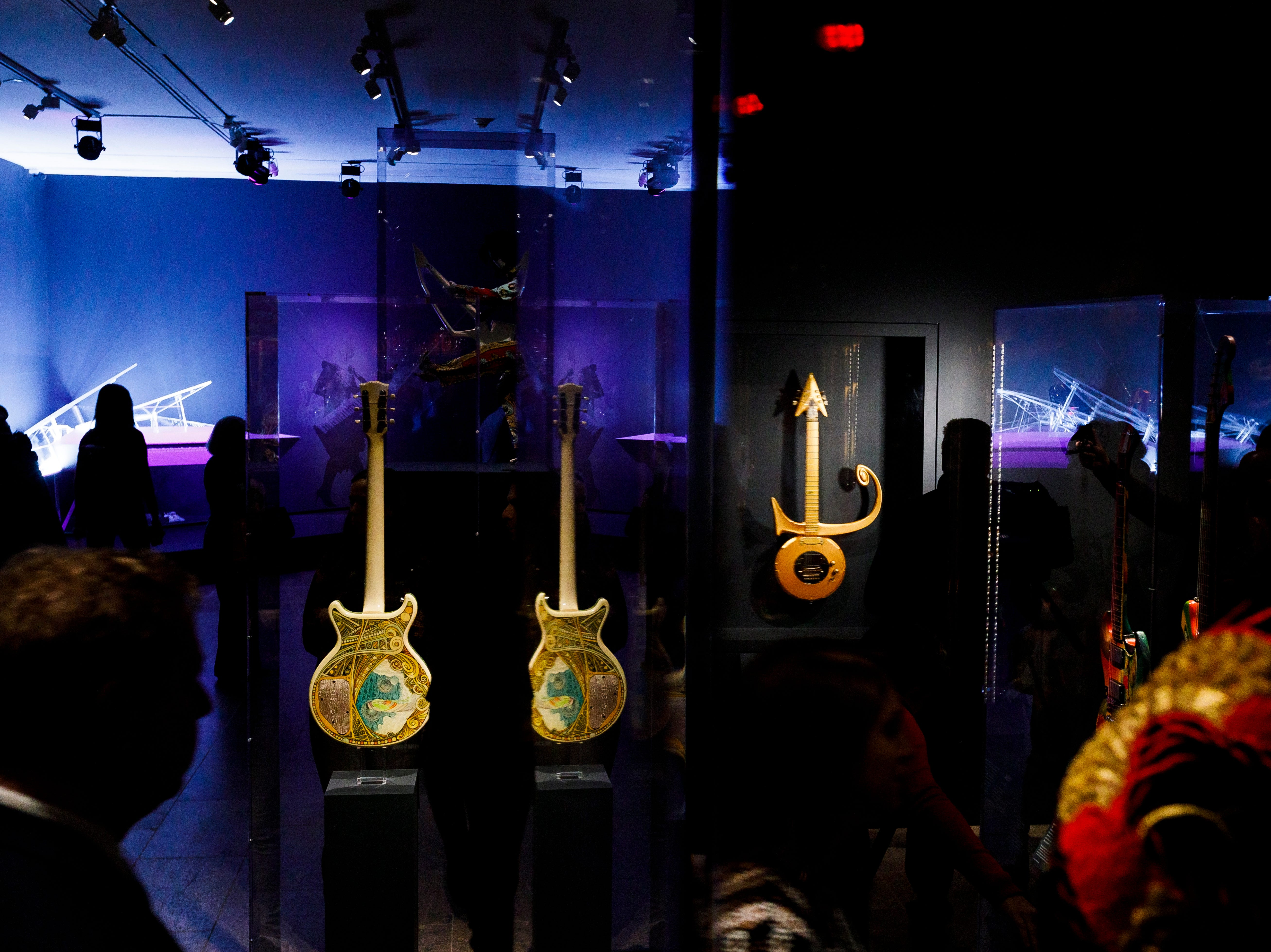 """People look at guitars played by Steve Miller, left, and Prince, right, as well as a piano played by Lady Gaga, background left, during a preview of the new exhibit """"Play It Loud: Instruments of Rock & Roll"""" at the Metropolitan Museum of Art."""