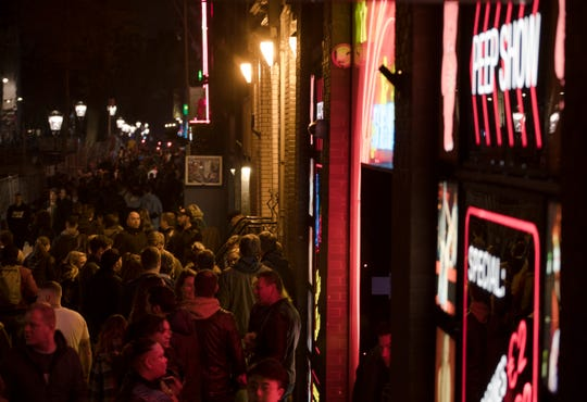 Tourists are bathed in a red glow emanating from the windows and peep shows' neon lights, packed shoulder to shoulder as they shuffle through the narrow alleys in Amsterdam's red light district, Netherlands on March 29, 2019.