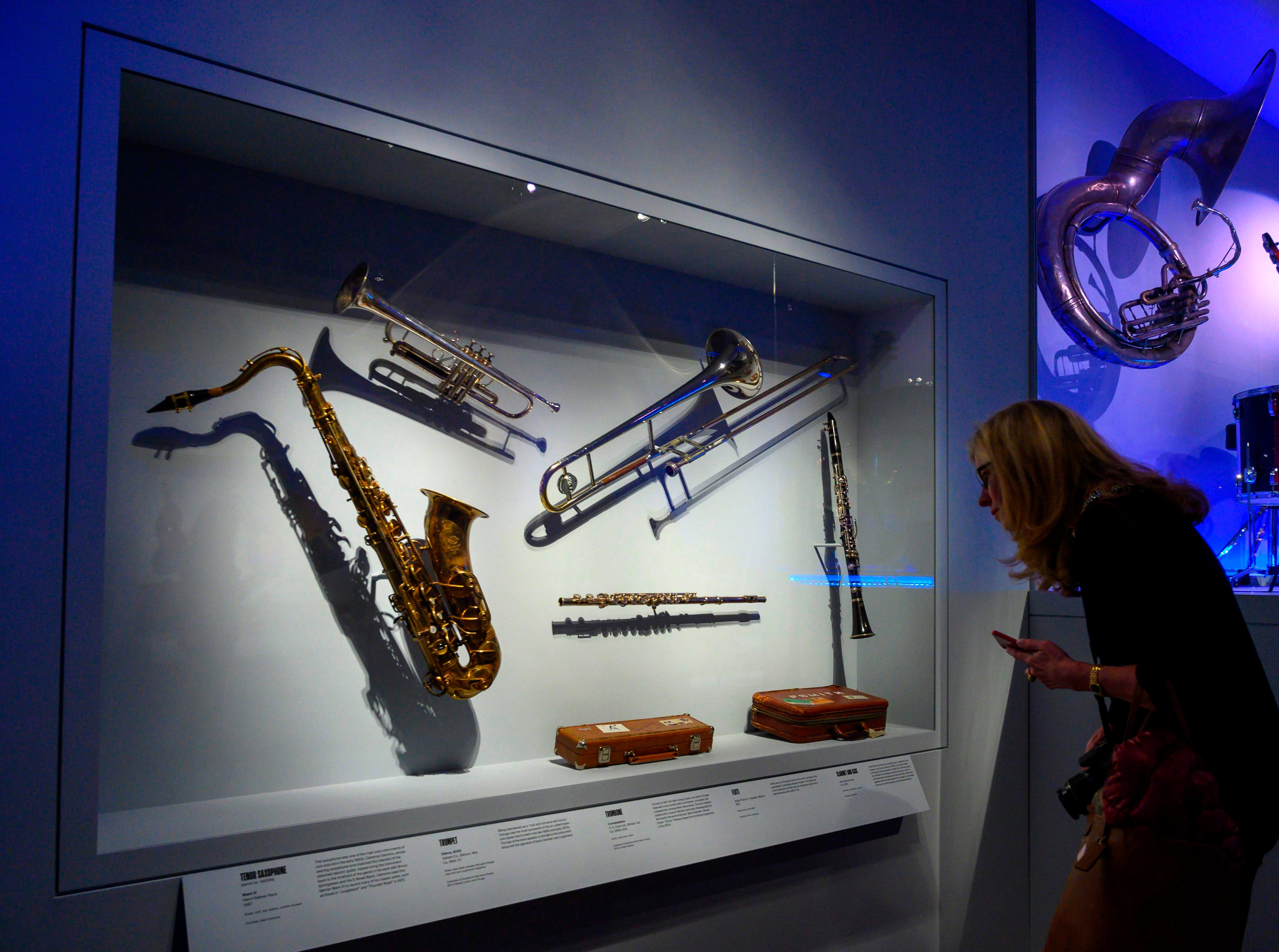 """A reporter looks at musical instruments during a media preview for an exhibit called """"Play It Loud: Instruments of Rock and Roll""""."""