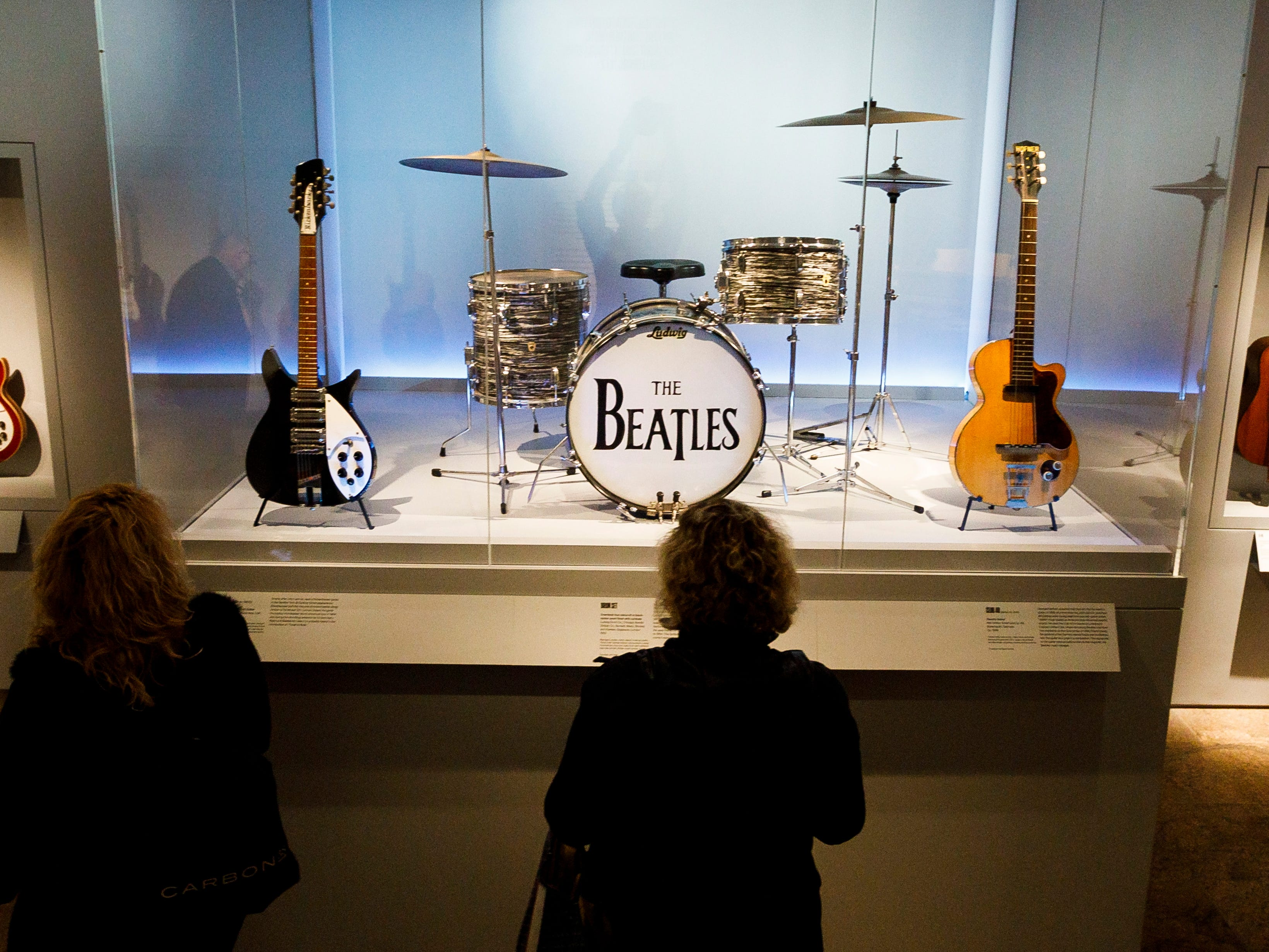 """People look at Ringo Starr's drum kit during a preview of the new exhibit """"Play It Loud: Instruments of Rock & Roll"""" ."""