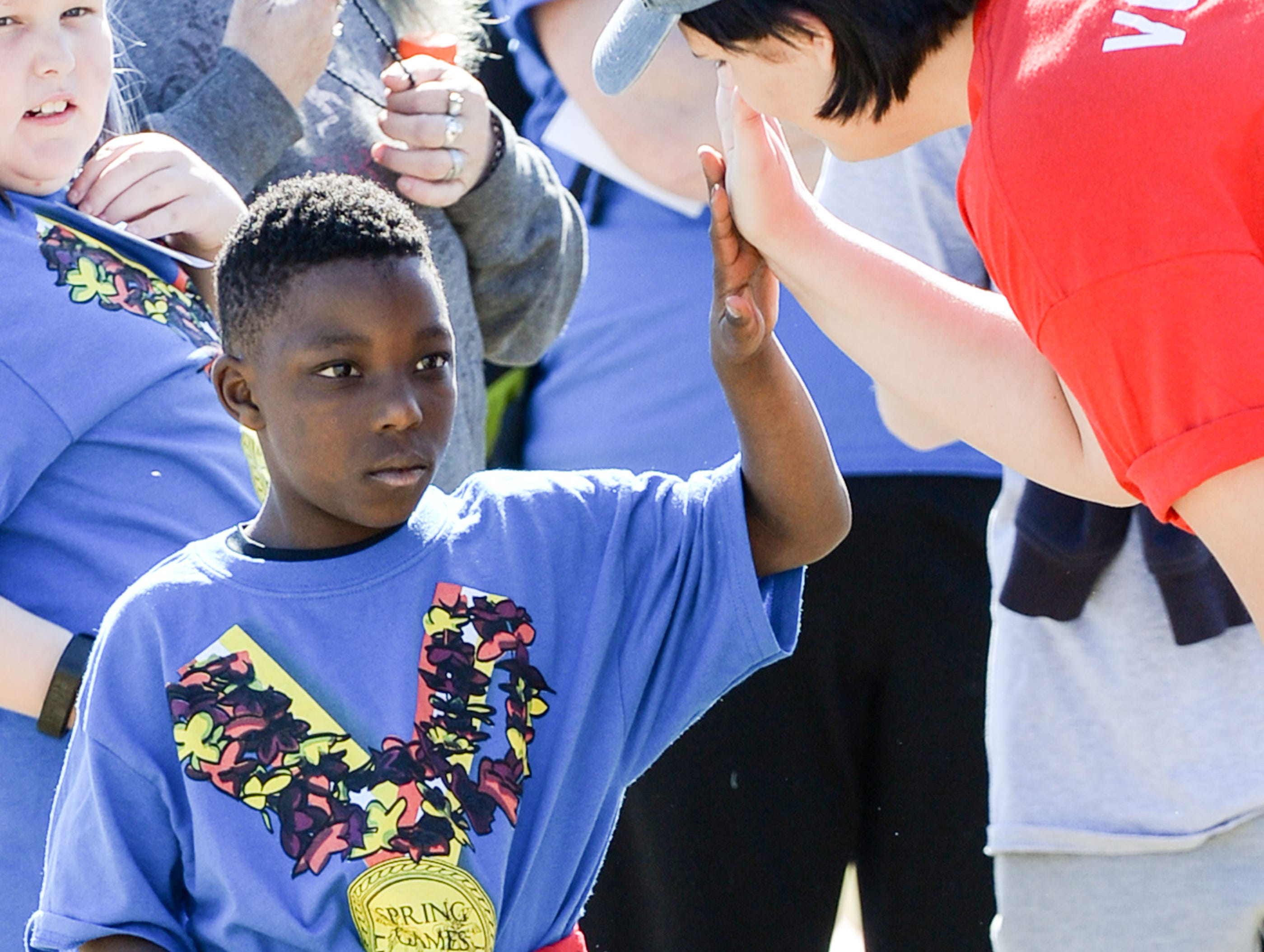 Xavier Woody of La France Elementary School, gives a high-five to volunteer Josie McCall, right, of Anderson University after throwing a softball during the Special Olympics South Carolina Area 14 Spring Games at Marlee Gambrell field at Belton-Honea Path High School Wednesday.