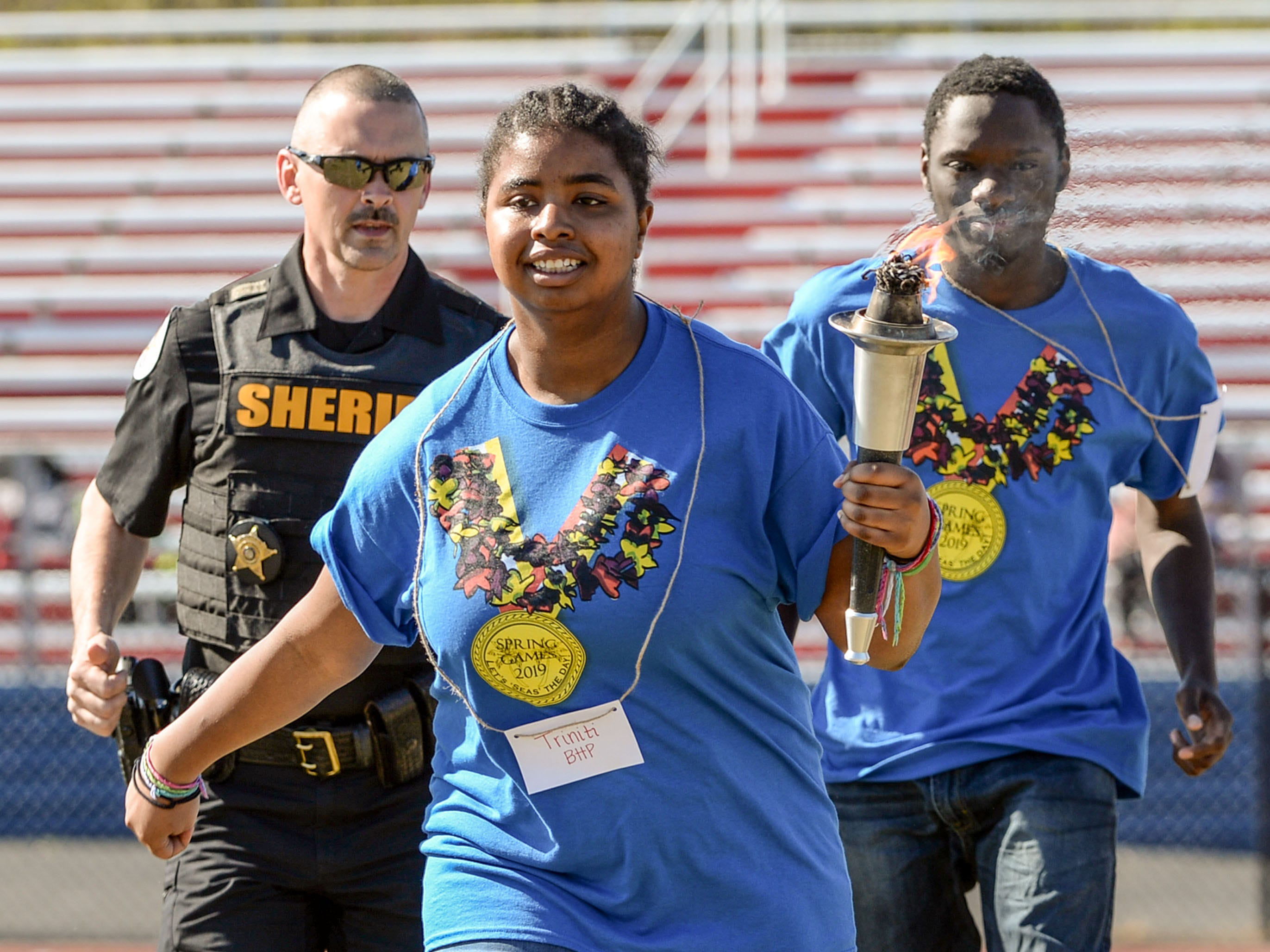 Capt. Bill Vaughn, left, of the Anderson County Sheriff's Office escorts athlete Triniti Fields, middle, and Jalen Martin, right, students from Belton-Honea Path High School, lighting the flame for the Special Olympics South Carolina Area 14 Spring Games at Marlee Gambrell field at Belton-Honea Path High School Wednesday.