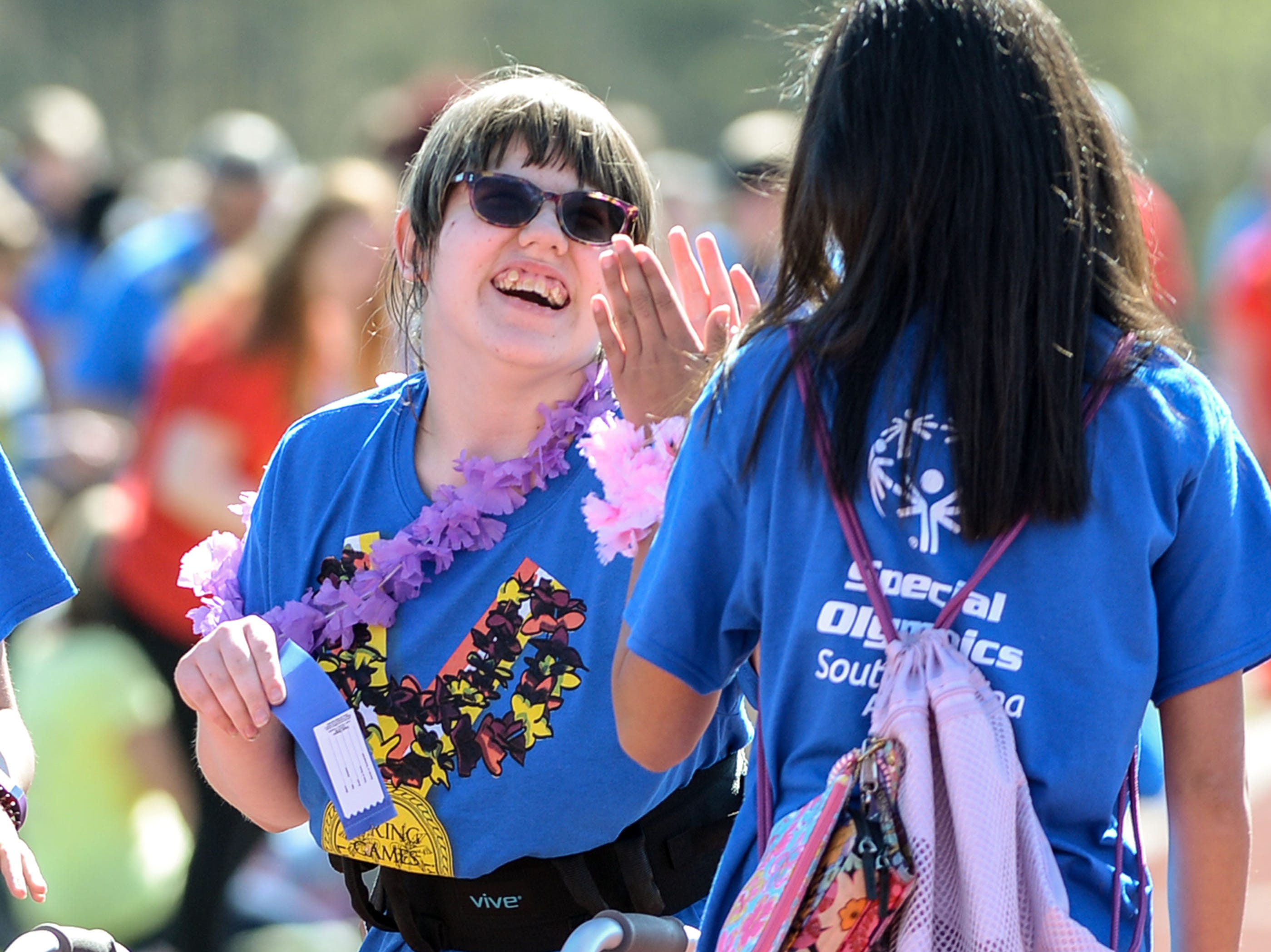 Volunteer Rachel Barth, right, of Palmetto Middle School, gets a high-dive from athlete Hollie Woodson after she won a blue ribbo in a 50 yard walk during the Special Olympics South Carolina Area 14 Spring Games at Marlee Gambrell field at Belton-Honea Path High School Wednesday.
