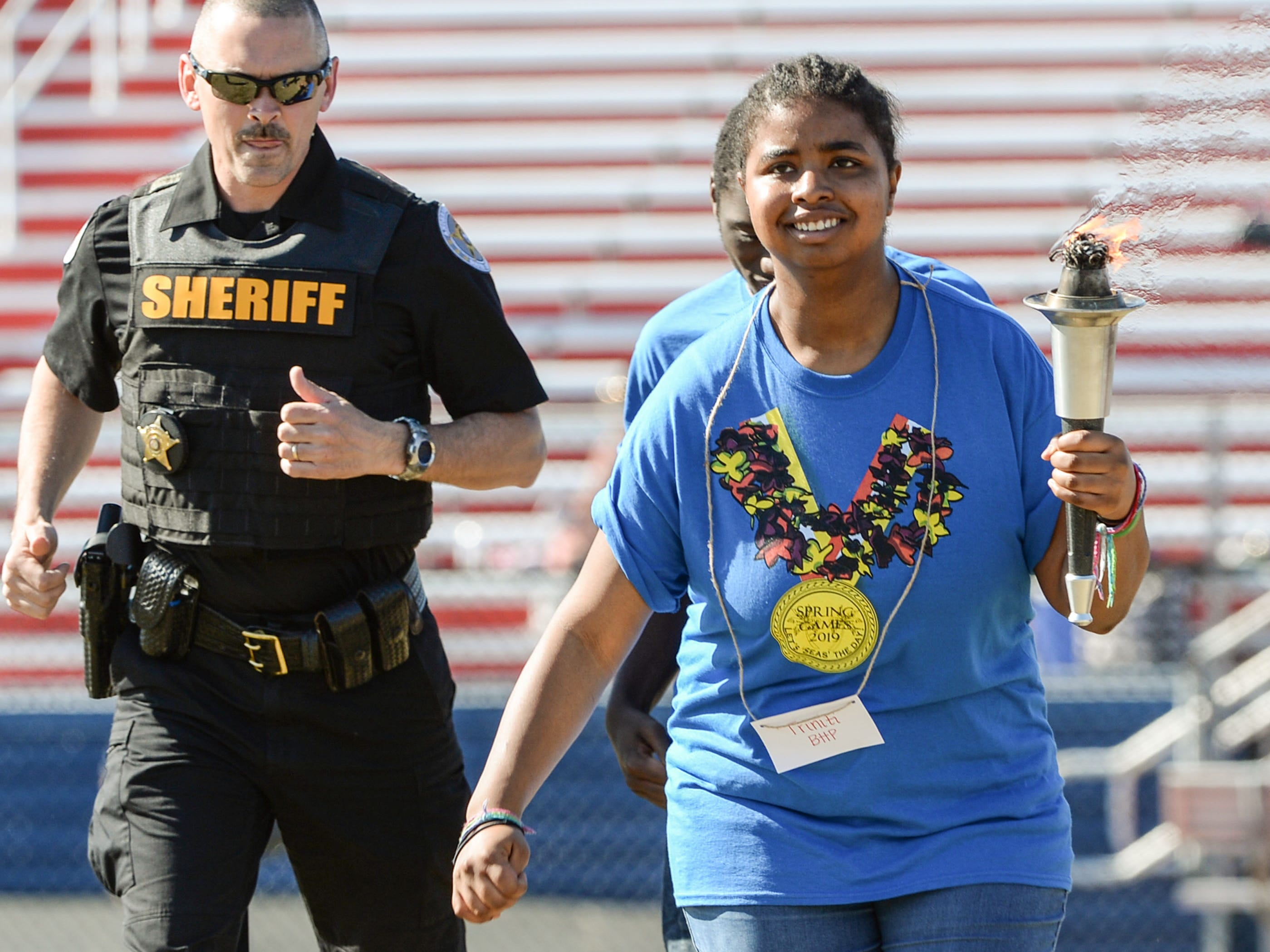 Capt. Bill Vaughn, left, of the Anderson County Sheriff's Office escorts athlete Triniti Fields, a student from Belton-Honea Path High School, to light the flame for the Special Olympics South Carolina Area 14 Spring Games at Marlee Gambrell field at Belton-Honea Path High School Wednesday.