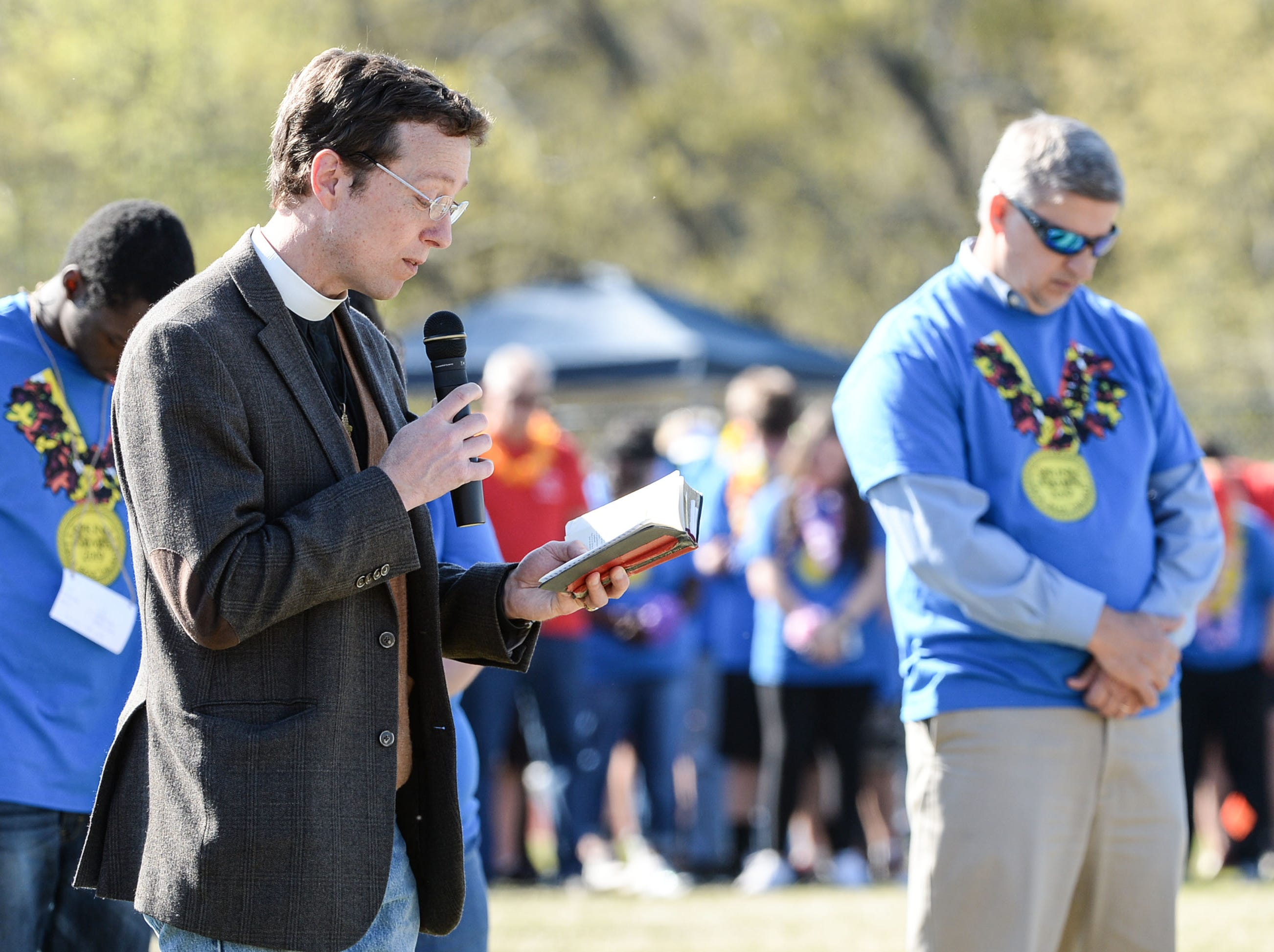 Father Jack Hardaway, left, of Grace Episcopal Church in Anderson, reads a prayer before the Special Olympics South Carolina Area 14 Spring Games at Marlee Gambrell field at Belton-Honea Path High School Wednesday.
