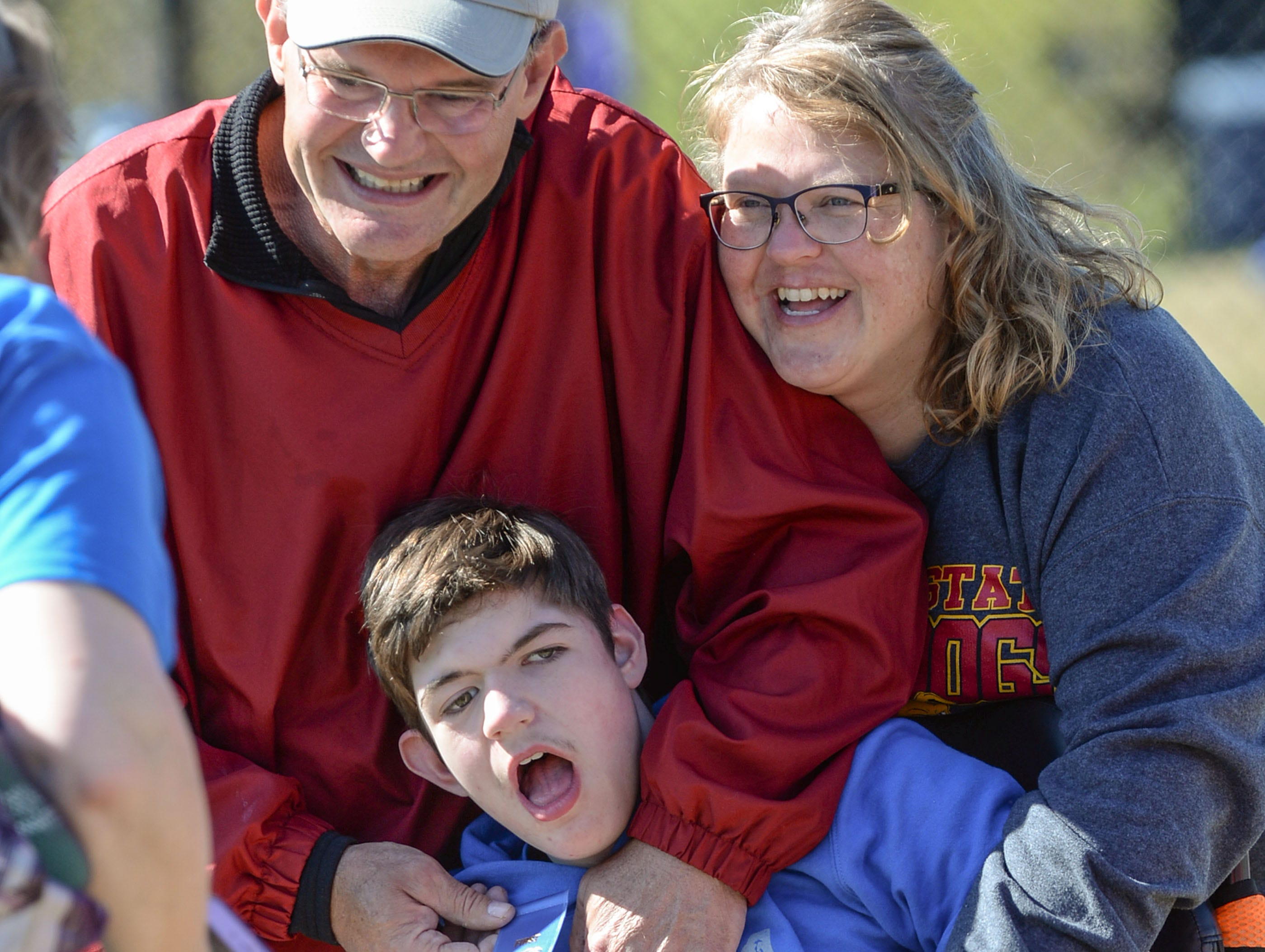 Jim and Angel Dotson hug their son Jacob of Flat Rock Elementary School in Starr, with a blue ribbon after softball throwing competition during the Special Olympics South Carolina Area 14 Spring Games at Marlee Gambrell field at Belton-Honea Path High School Wednesday.