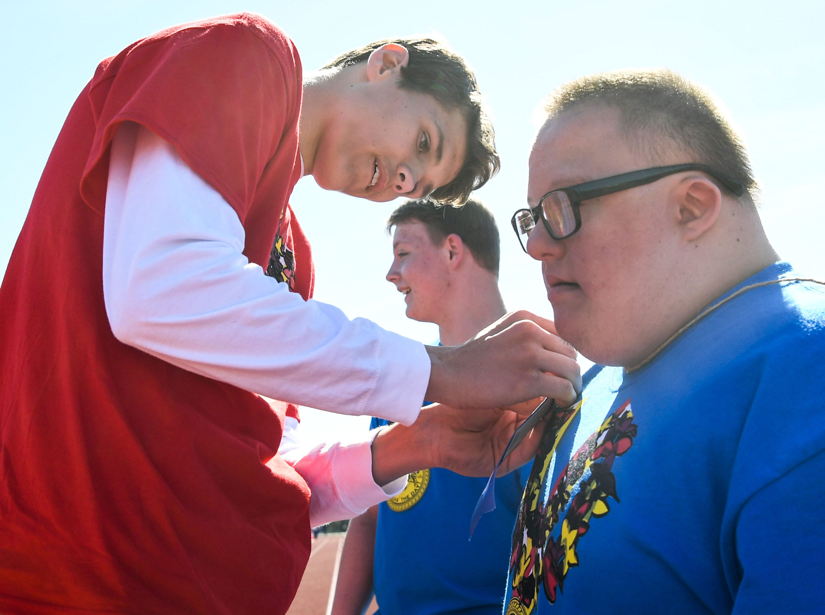 Volunteer Dodson Wood, left, a junior at Belton-Honea Path High School places a blue ribbon on athlete Cody Darby after the 100 yard walk during the Special Olympics South Carolina Area 14 Spring Games at Marlee Gambrell field at Belton-Honea Path High School Wednesday.