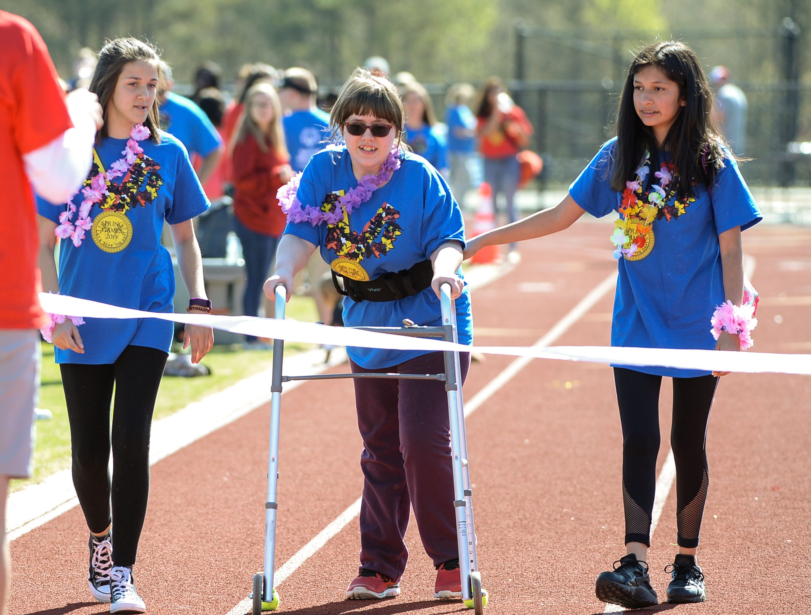 "Volunteers Leslie Terrazaas, left, and Rachel Barth, both of Palmetto Middle School, escort Hollie Woodson across the finish line in a 50 yard walk during the Special Olympics South Carolina Area 14 Spring Games at Marlee Gambrell field at Belton-Honea Path High School Wednesday. The event had more than 800 athletes and nearly 1,000 volunteers said Principal Lester McCall of Belton-Honea Path High School. ""It's a huge community event,"" he said."