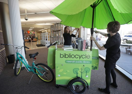 Neenah Library Director Gretchen Raab, right, and Assistant Library Director Nicole Hardina-Wilhelm set up the library's Bibliocycle for display inside the library. The book bike will be put to use later this month.