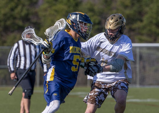 Toms River North's Trevor Foss drives in towards goal against Brick Memorial's Jackson Forsyth. Toms River North Boys Lacrosse vs Brick Memorial in Brick N.J. on April 3, 2019.