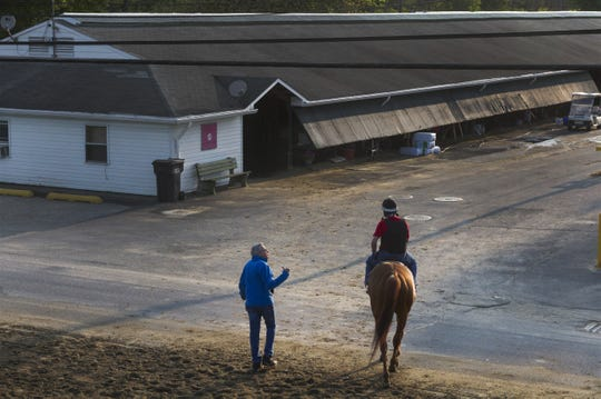 Trainer Chuck Spina talks with his rider as they head back to stable after one of his horse's morning workouts in 2016.