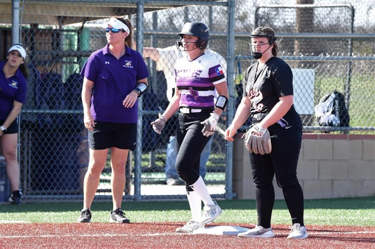 Wylie's Lilly New (16) stands next to coach Heather Collier after reaching third base on a wild pitch against Aledo on Tuesday, April 2, 2019. The Lady Bulldogs won 3-1 to remain tied for first place in District 4-5A.