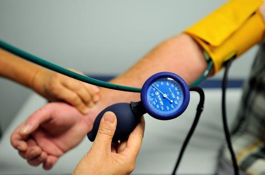 A nurse measures the blood pressure of a patient.