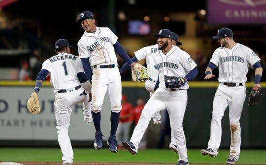 Seattle Mariners' Tim Beckham (1), Mallex Smith, Domingo Santana and Mitch Haniger celebrate after the team beat the Los Angeles Angels in a baseball game, Tuesday, April 2, 2019, in Seattle. The Mariners won 2-1.