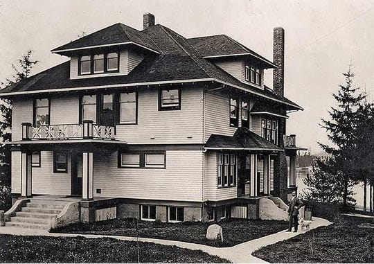 The Nordby mansion, which later became the Cedar Cove Inn, was built in 1907. Gil and Kathy Michael renovated the home in the 1990s and turned it into a bed and breakfast. This photo shows the home in its original layout with Peter Nordby, founder of Kitsap Bank, standing on the sidewalk.
