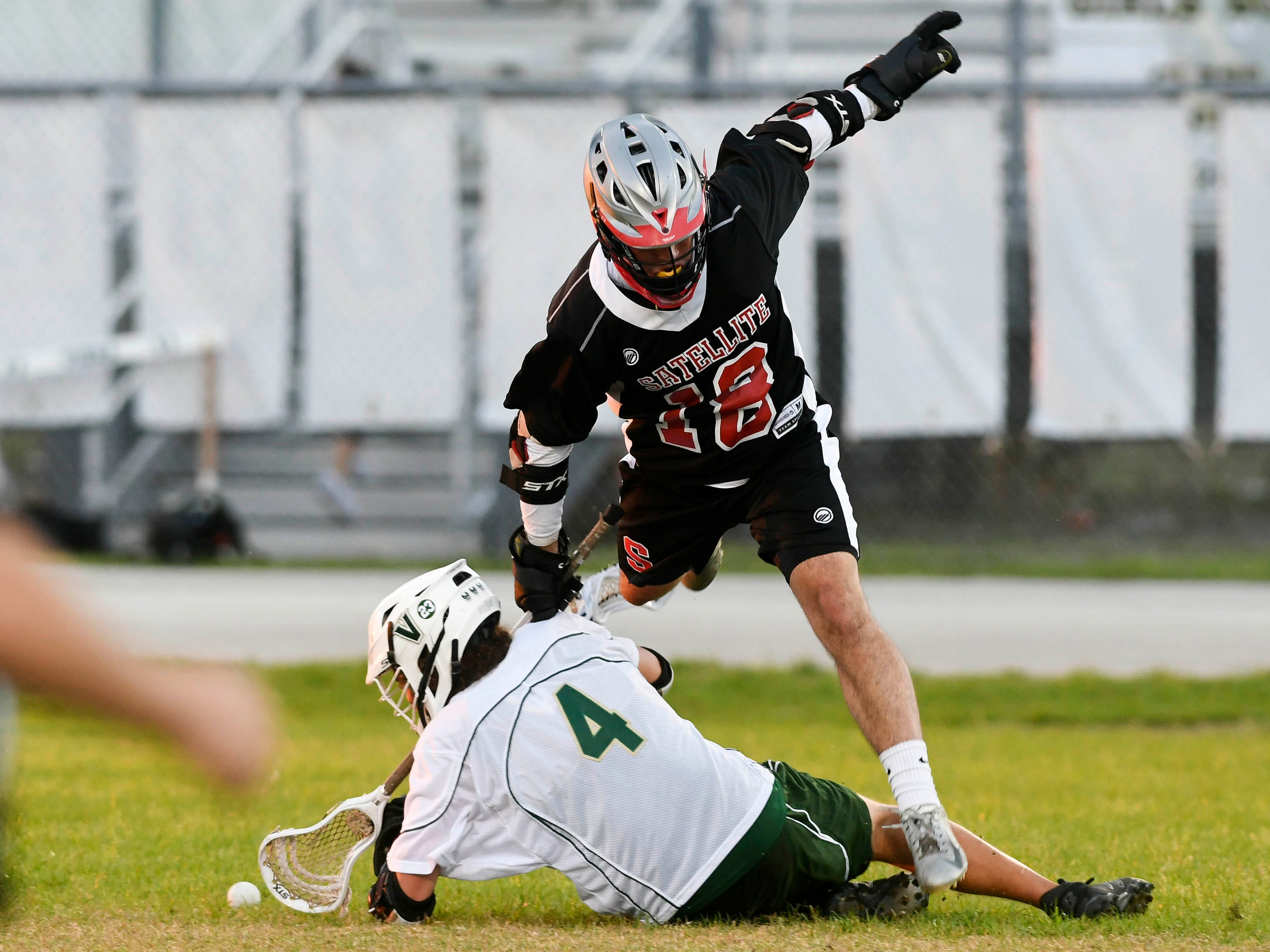 Satellite's Damon Denan leaps Gavin Wessell of Viera during Tuesday's game.