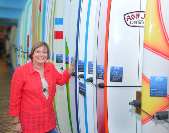 Ron Jon President Debbie Harvey stands by a row of longboards on the second floor of the Cocoa Beach store. Ron Jon Surf Shop will celebrate its 60th anniversary this year, with events planned for the summer.