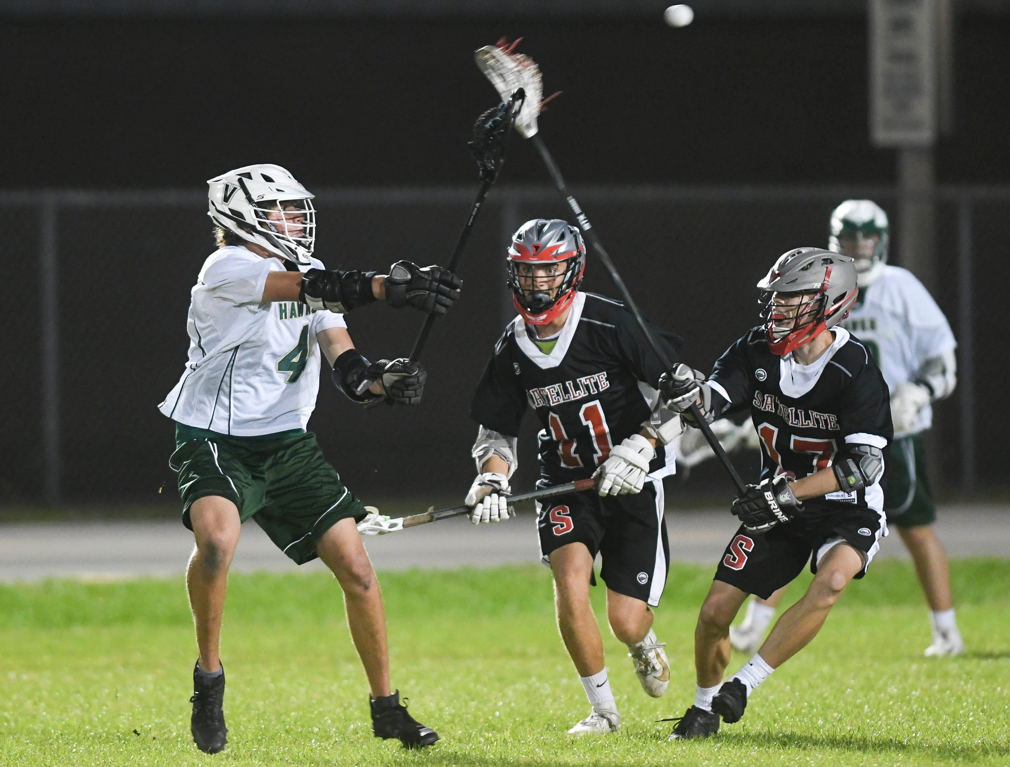 Gavin Wessell of Viera (4) passes away from a pair of Satellite defenders during Tuesday's game in Viera