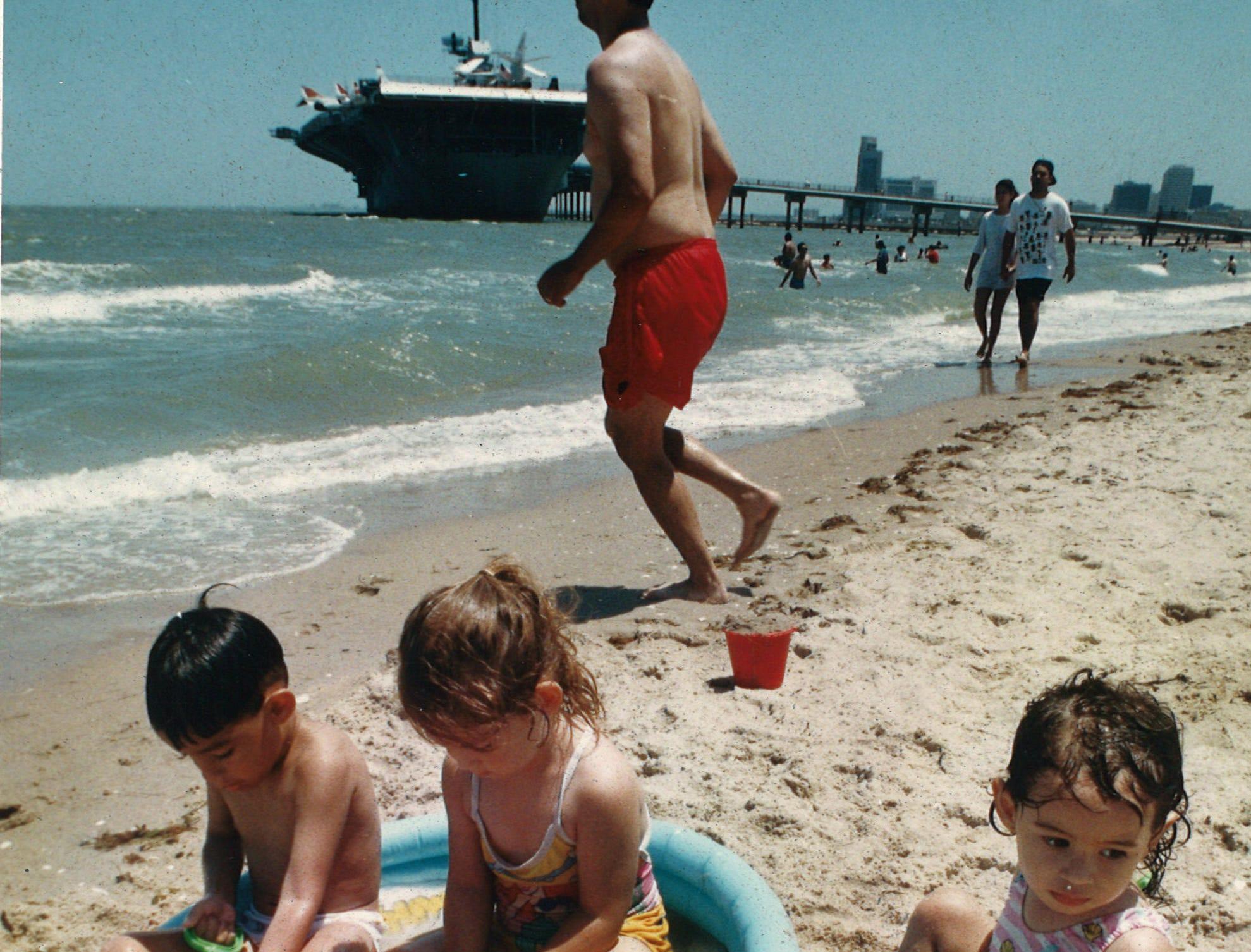 Joshua Garza, 4,; Dawn Quiroz, 3,; and Monica Garza, 2, use a small wading pool at the edge of the water at Corpus Christi's North Beach on May 30, 1995.
