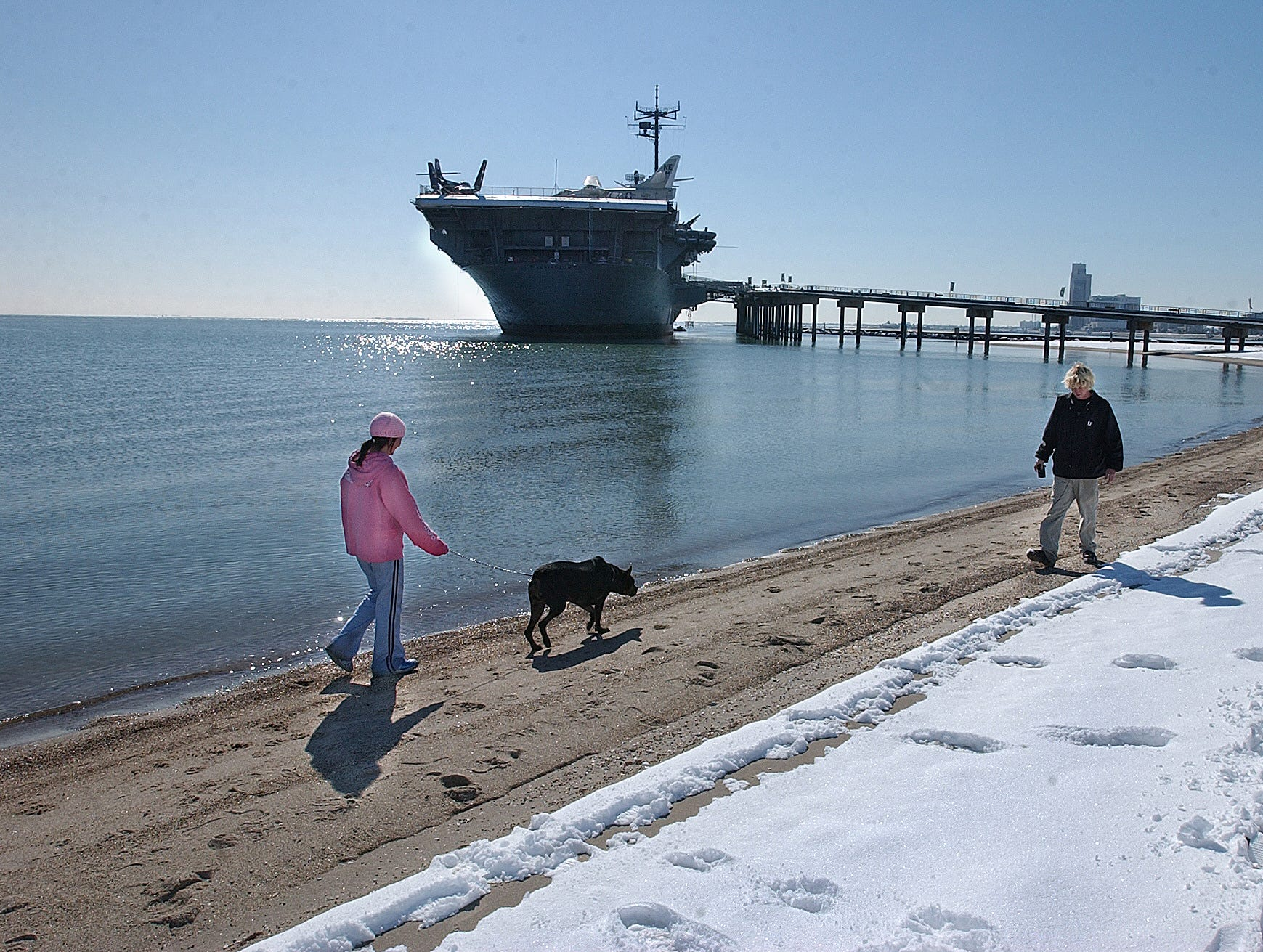 April Burges (left) and Tommy Lonnon walk their mixed pit bull, Hooch, along Corpus Christi Beach early Saturday morning, Dec. 25, 2004. The couple said it was the first time Hooch had experienced snow.