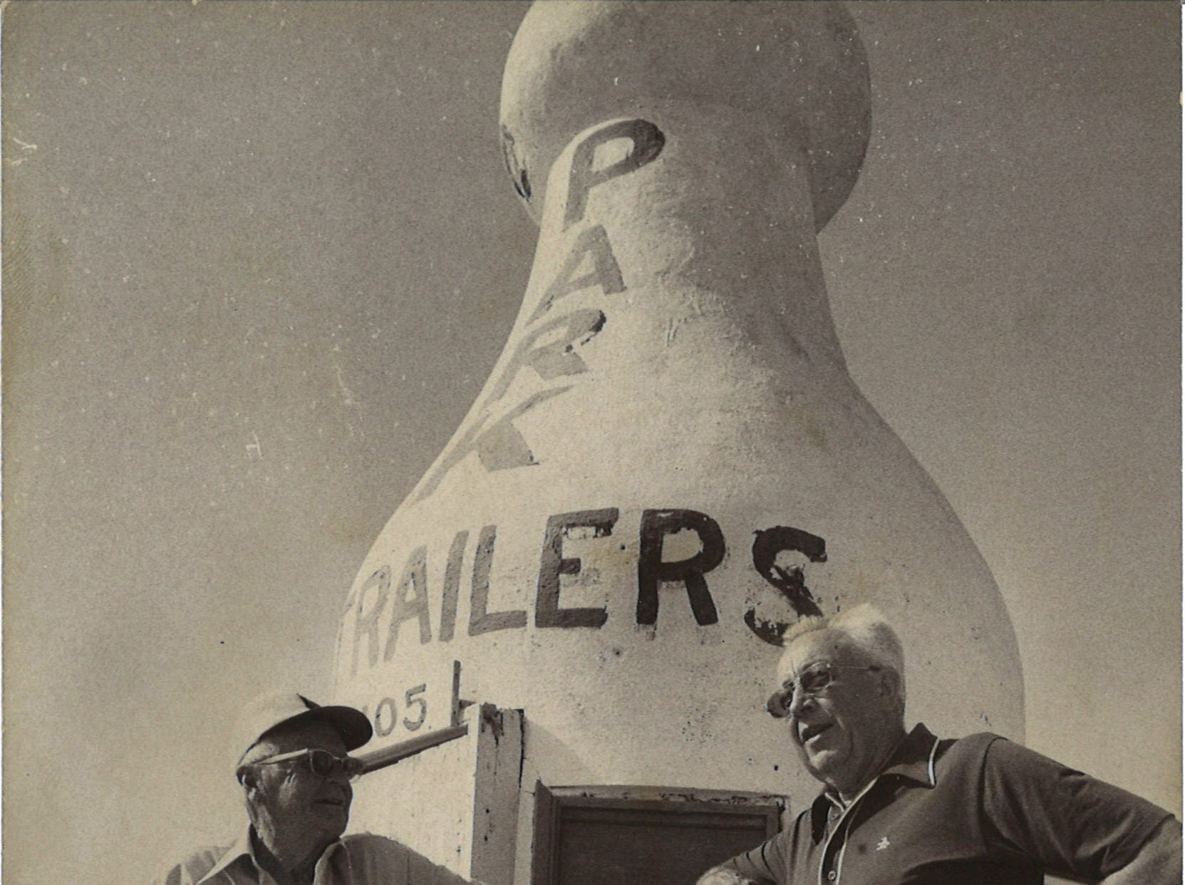 Winter Texans Jerome Quam of Wisconsin (right) and Bernard Mercer of Iowa (left) lounge next to the large cement milk bottle painted to advertise Park Trailers at 4105 Timon Blvd on Corpus Christi's North Beach in April 1976.