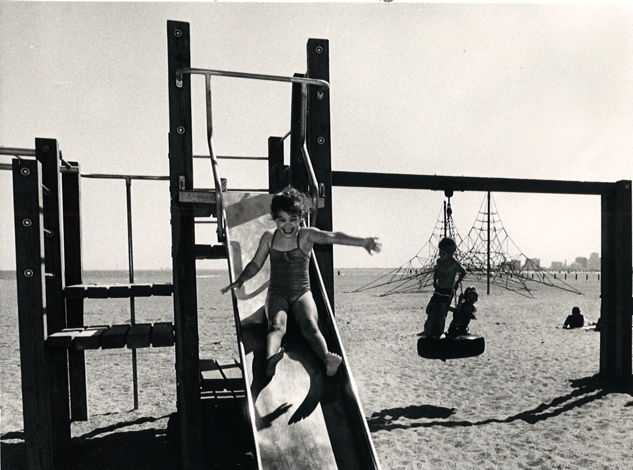 Sarah Briscoe, 4, slides down the playground equipment at Corpus Christi's North Beach as John Magill, 4, and Jana Magill, 2, play on a tire swing on March 17, 1986.