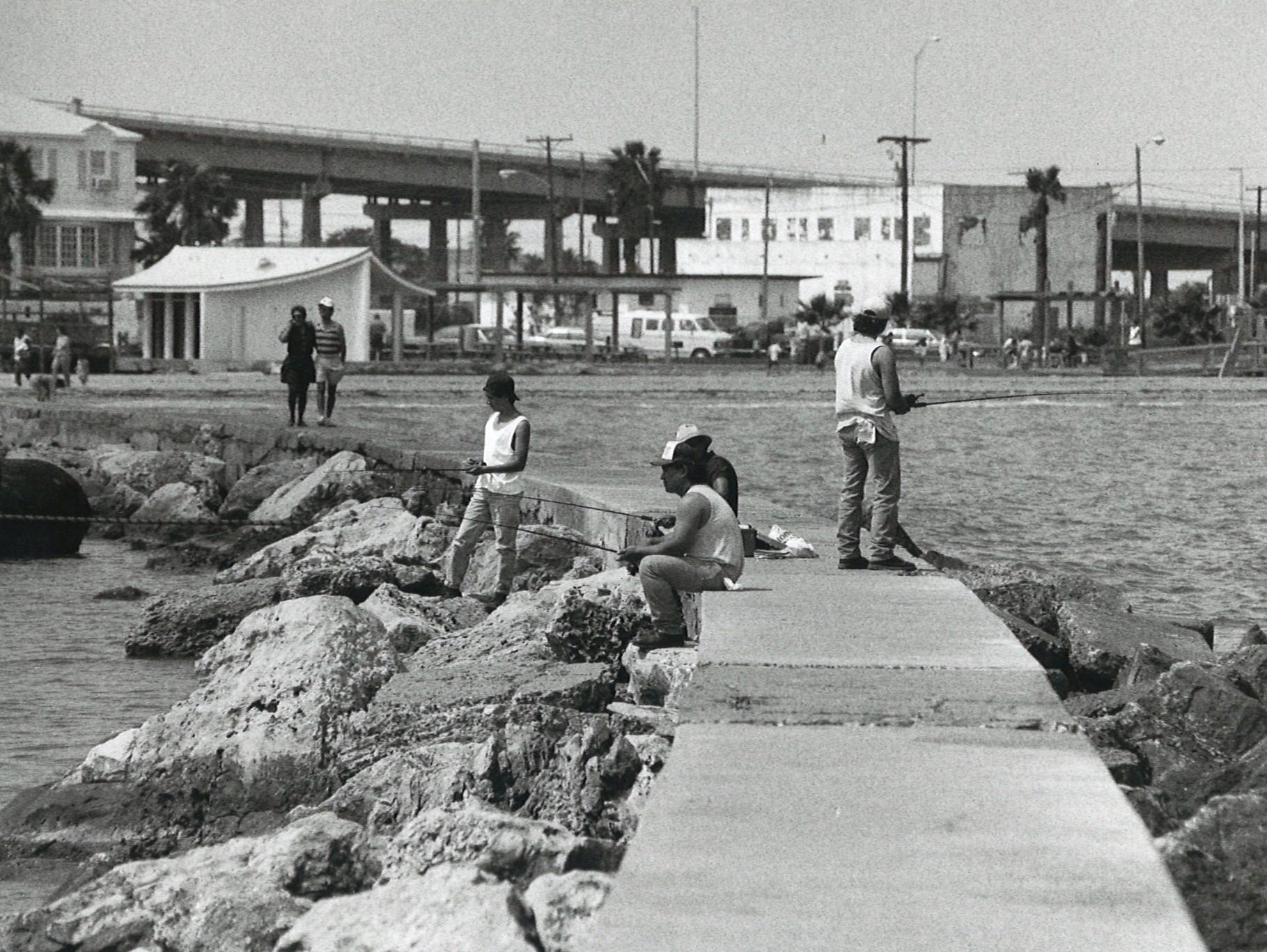 Fishermen enjoy the pleasant weather at the jetties on the south end of Corpus Christi's North Beach next to the Texas State Aquarium on March 29, 1992.