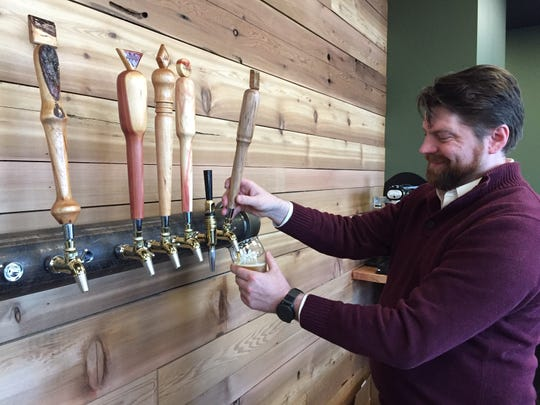 Axe & Arrow Microbrewery co-founder Greg Fletcher of Pedricktown pours a beer from the taps in the tasting room.